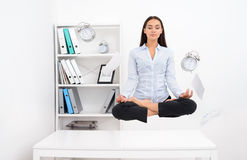 Woman levitating above office desk and meditating in lotos position. Young calm brunette business woman levitating above office desk and meditating in lotos Stock Images