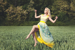 Woman levitating over the field on a sunny day. Stock Photo