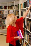 Woman in library. Pretty Woman picking out a book from a library shelf Royalty Free Stock Photo