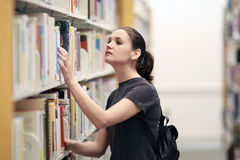 Woman in the library. Searching for the book Stock Images
