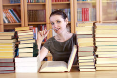 Woman in the library. Reading the book Royalty Free Stock Images