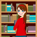 Woman In Library. Beautiful brunette librarian woman in library holding books Stock Images