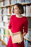Woman in library with book looks away Royalty Free Stock Photography