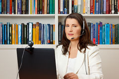 Woman library computer headset webcam. Middle aged woman with headset in front of her computer with webcam in a library, consultant, teacher, tutor, online Royalty Free Stock Image