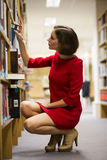 Woman in library found book for reading Stock Image