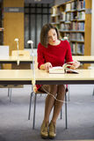 Woman in library leaf through fat book Stock Photo
