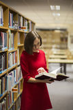 Woman in library near shelves with book Royalty Free Stock Photo