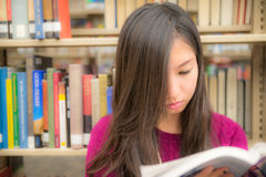 Woman in library. Woman reading a book next to a book shelf in library Stock Photography