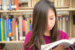 Woman in library. Woman reading a book next to a book shelf in library Stock Photo