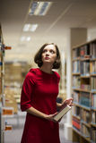 Woman in library between shelves with book Stock Image