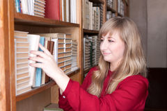 Woman in the library takes the book Stock Photo