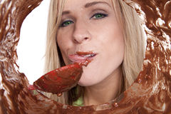 Woman licking batter bowl Stock Images