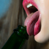 Woman licking bottle. Closeup view of female facial body part of sexual lips with bright red lipgloss licking with tongue in open mouth green color glass wine stock photos