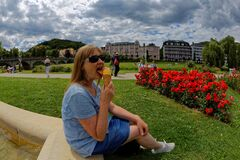 Woman licking ice cream in park at edge of fountain basin summer holidays 2020