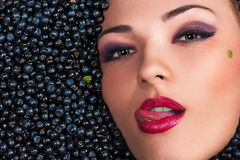 Woman licking lips lying in blueberries. Beautiful woman licking lips lying in blueberries Royalty Free Stock Image