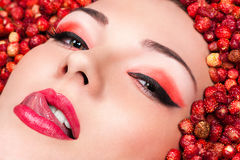 Woman licking lips lying in wild strawberries. Sensual woman licking lips lying in wild strawberries Stock Photography