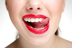 Woman licking teeth with tongue. Close up portrait of a woman licking teeth with tongue royalty free stock photos