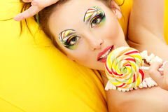 Woman licks candy with beautiful make-up. On yellow sofa Royalty Free Stock Images