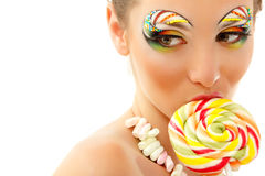 Woman licks candy with beautiful make-up. Isolated on white background Stock Photos