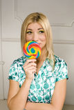 Woman licks candy with beautiful make-up Royalty Free Stock Images