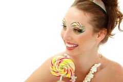 Woman licks candy with beautiful make-up isolated on white. Background. Sexy girl with sweet candy Royalty Free Stock Photos
