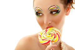 Woman licks candy with beautiful make-up isolated on white. Background. Sexy girl with sweet candy Royalty Free Stock Images