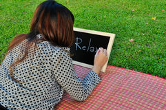 Woman lie down on grass and write on blackboard Royalty Free Stock Photography