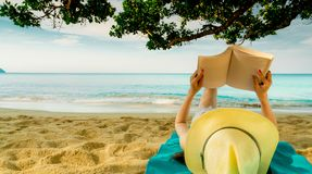 Woman lie down on green towel that put on sand beach under the tree and reading a book. Slow life on summer vacation. Asian woman royalty free stock photos