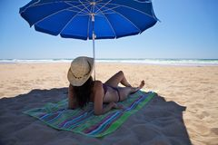 Woman lie down under parasol Stock Images