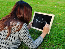 Woman lie down and write word on the blackboard. Woman lie down on the grass and write relax word on the blackboard Royalty Free Stock Image