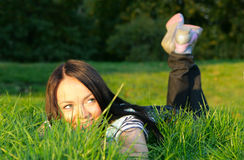 Woman lie on grass. Young happy woman lie on the grass at evenings Royalty Free Stock Image