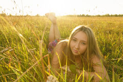 Woman lie on the grass. Young cute woman lie on the grass in the field Royalty Free Stock Photography