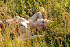 Woman lie on the grass. Young cute woman lie on the grass in the field Stock Photography