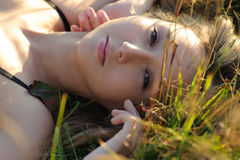 Woman lie on the grass. Young cute woman lie on the grass in the field Stock Image