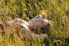 Woman lie on the grass. Young cute woman lie on the grass in the field Royalty Free Stock Image