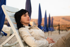 Woman lie in lounge on the stone. Woman lie in chaise longue on the stone beach in the evening Royalty Free Stock Image
