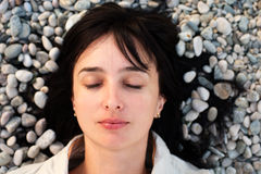 Woman lie on the stone beach Stock Image