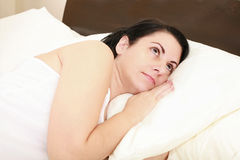 Woman lies awake in bed. A young woman lies awake in bed. Sleepless and thoughtful Stock Images