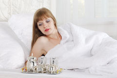Woman lies on bed with white linen Stock Photography