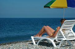 Woman lies in chaise longue on beach Stock Photography