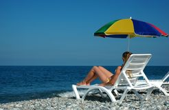 Woman lies in chaise longue on beach Stock Photos