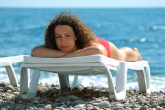 Woman lies in chaise lounge. Young woman lies in chaise lounge on the beach Royalty Free Stock Photography
