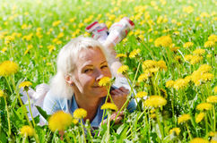 Woman lies in a clearing and sniffs a flower Royalty Free Stock Photo