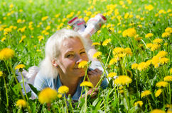 A woman lies in a clearing and sniffs a flower Stock Photography