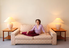 Woman lies on couch in simple comfortable room Stock Images