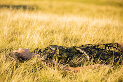 Woman lies down in the grass Stock Image