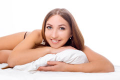 The woman lies on the edge of the bed and smiling , with her head resting on the pillow . The hands are under the pillow Royalty Free Stock Photos