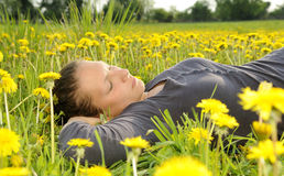 Woman lies on a flower meadow Stock Photography