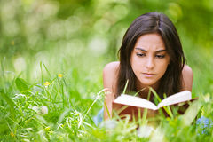 Woman lies on grass and reads book Royalty Free Stock Images