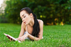 Woman lies on grass and reads book Royalty Free Stock Image